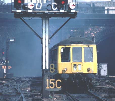 A DMU comes out from a fume filled Gas works tunnel