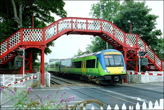 Central Trains class 170 comes under the footbridge and over the level crossing in 2003