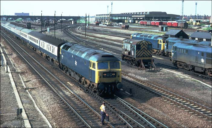 A class 47 comes into Peterborough past the small Depot with a platelayer stood on the down fast.