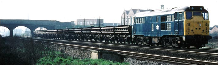 A class 31 with a train of ballast wagons at Fletton