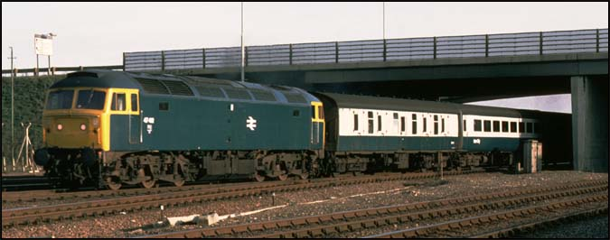 A class 47 on a down train comes under the A47 road bridge at Walton on the ECML