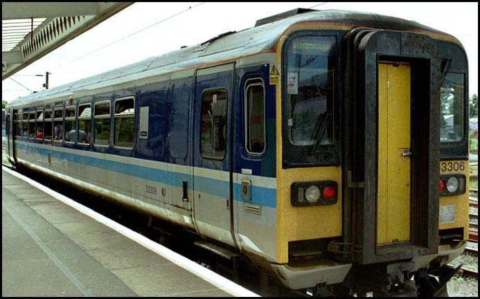 Class 153306 is in platform 5 at Peterborough in 2004 still in its BR  regional railway colours of grey and blue.