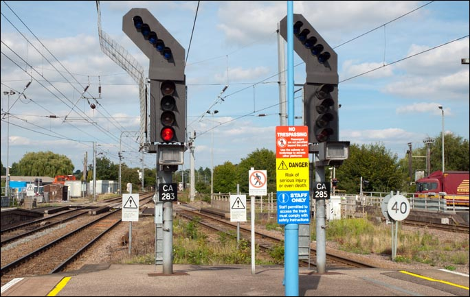 Two of the signals and signs at the north end of Ely station in 2013